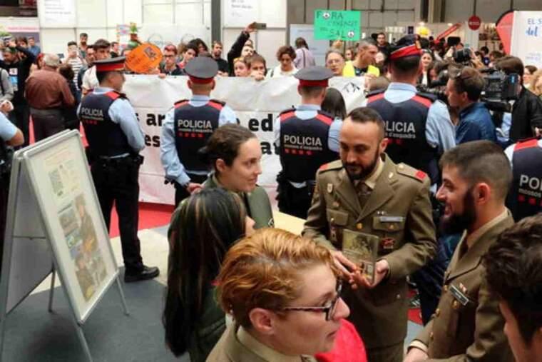 Membres de la plataforma Desmilitaritzem l'Educació protestant davant de l'estand de l'Exèrcit