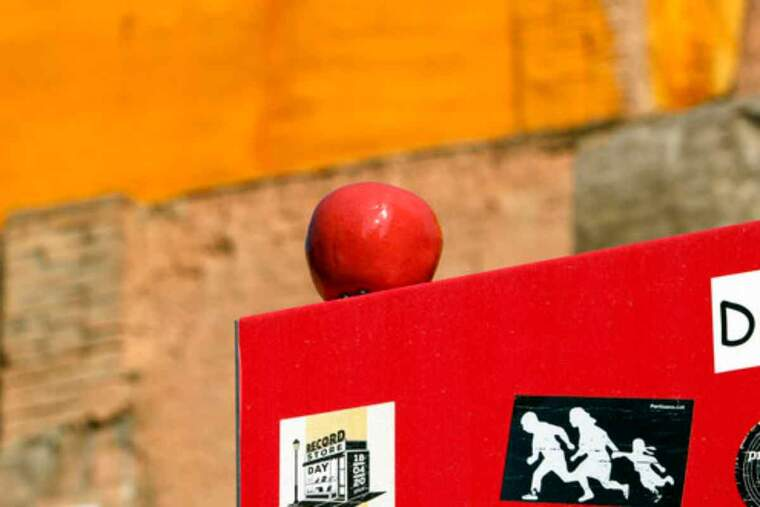 Pla curt on es pot veure una poma de ceràmica al capdamunt d'un cartell en el marc de la intervenció artística 'El preu de la fruita'