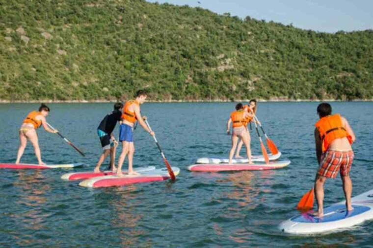 Pla obert amb un grup de joves practicant una activitat aquàtica al pantà de Rialb