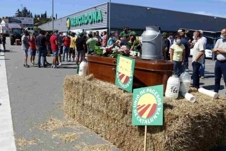 En un primer pla del taüt i garrafes de palla amb la mobilització dels pagesos de fons davant el Mercadona
