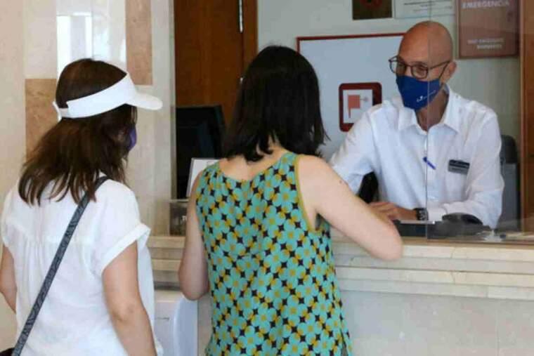 Pla mitjà de la recepció d'un hotel, amb dues clientes fent una gestió