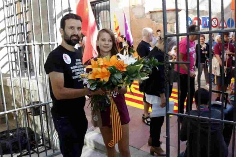 Pla mig on es pot veure el regidor de la Crida-CUP de Lleida, Pau Juvillà, acompanyat d'una jove fent l'ofrena floral de la Diada al Roser