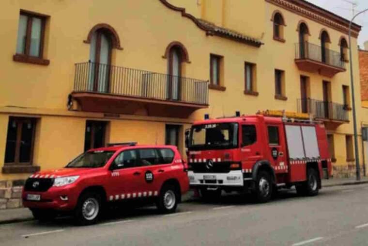 Pla obert on es poden veure els vehicles dels Bombers Voluntaris de Seròs aparcats al davant de l'alberg municipal