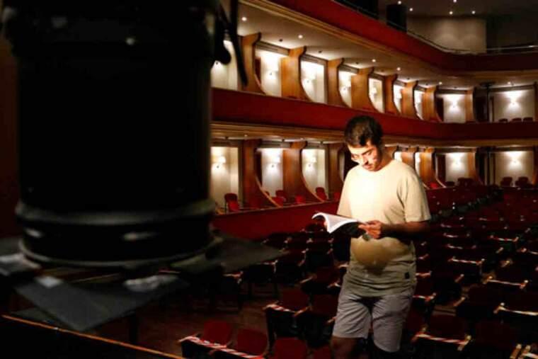 Pla obert on es pot veure Jordi Bonilla, autor del llibre 'Cançons entre bancals', fullejant un exemplar a l'escenari del teatre l'Amistat de Mollerussa