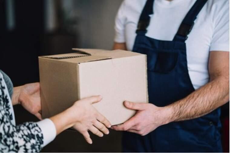 Repartidor entregando una caja de cartón a una mujer