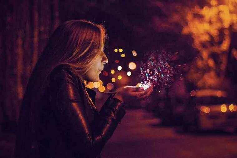 Chica en la calle soplando polvos de colores de entre sus manos