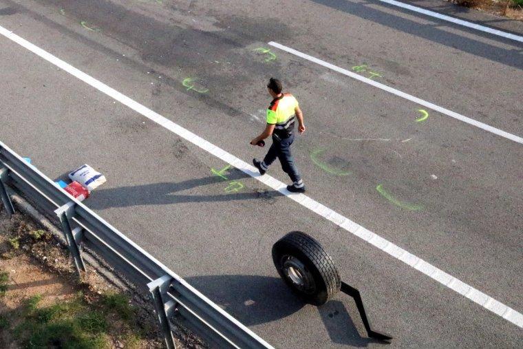 Pla detall d'un agent dels Mossos passant pel costat d'una roda de grans dimensions, en l'accident mortal que s'ha produït a l'AP-2 a Vila-rodona.