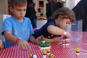 Dos nens jugant a apilar taps com si siguin castells, durant la Fira Castells