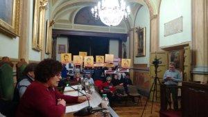 La portaveu del PSC, Rosa Maria Ibarra, amb els cartells a favor de l'alliberament dels presos polítics de fons.