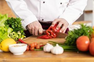 Fotografía de una persona cortando verduras en la cocina