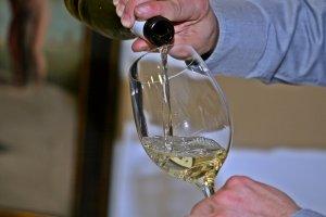 Un sommelier servint una copa de vi blanc