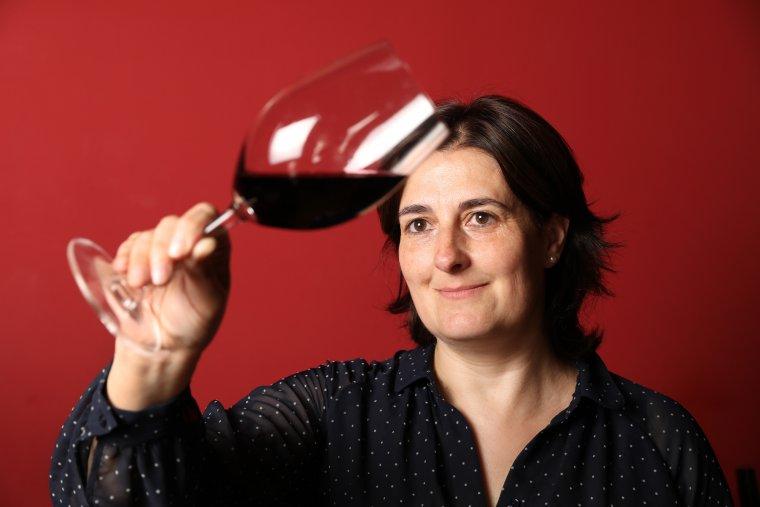 La sommelier Raquel Pérez observa el color d'un dels vins negres que té a la carta del restaurant