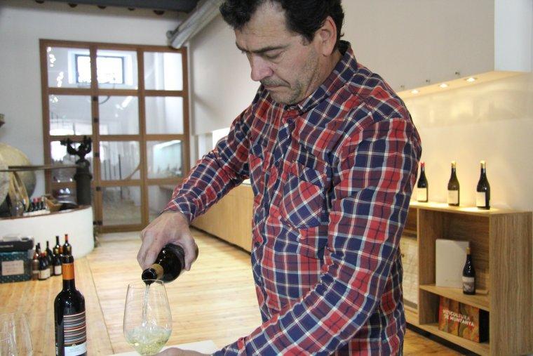 Tomàs Cusiné serveix una copa de vi al celler que porta el seu nom