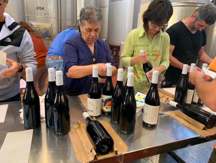 Voluntaris etiquetant les ampolles de Masroig Vi Solidari 2019