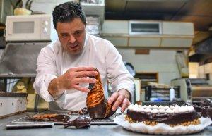 Ramón De la Fuente, propietari de la Pastisseria Huguet, muntant la figura del Basilisc de xocolata.